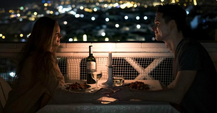 đôi tình nhân đang hẹn hò lãng mạn dưới ánh nến và rượu vang.