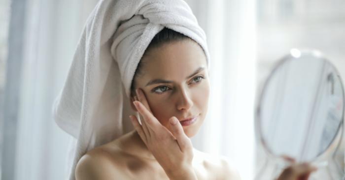 cô gái đang ngắm mình trong gương sau khi đã tẩy trang và chuẩn bị dưỡng da cho làn da khỏe mạnh
