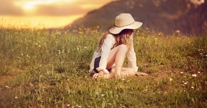 Cô gái ngồi buồn trên cánh đồng nhớ về kỷ niệm đã qua.