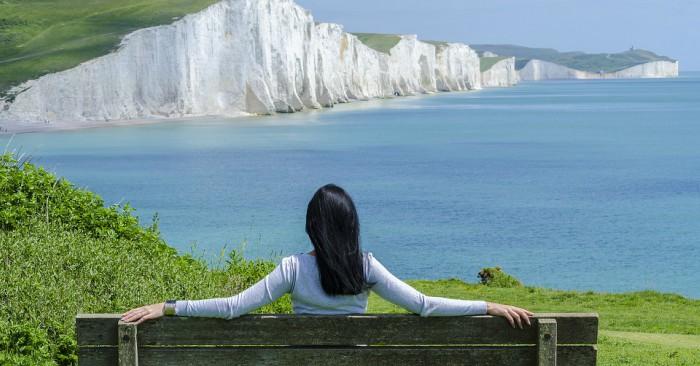 Người phụ nữ đang thả hồn ngắm cảnh đẹp thiên nhiên trên bờ biển.