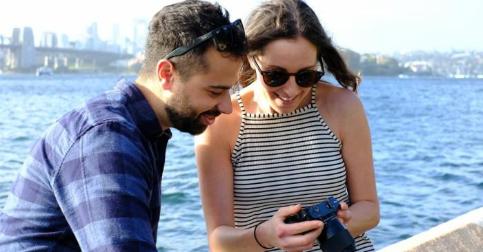 Trên bờ biển người phụ nữ đang cho người đàn ông xem bức ảnh mình vừa chụp.