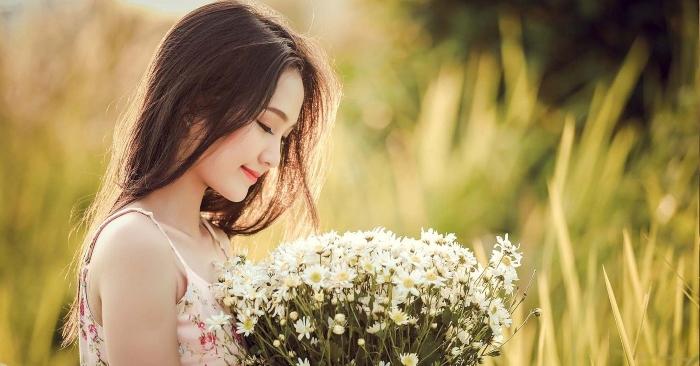 Người phụ nữ xinh đẹp. mỉm cười bên hoa cúc họa mi.