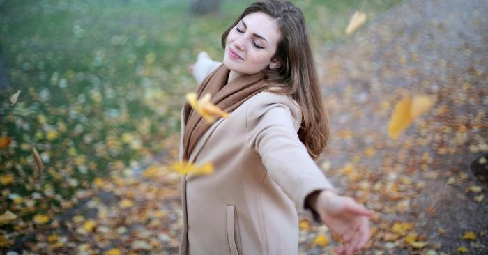 Người phụ nữ mỉm cười hạnh phúc, dang rộng vòng tay như muốn ôm lấy cả đất trời.