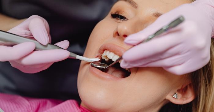 Nha sỹ đang khám răng cho nữ bệnh nhân, để đánh giá tình trạng sức khỏe răng miệng.