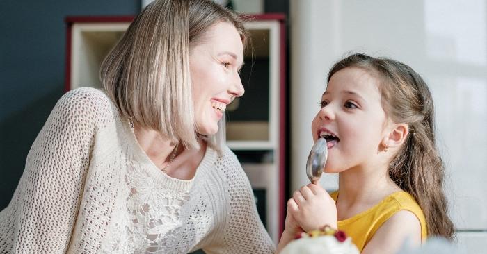 mẹ và bé gái đang thưởng thức thành quả làm bánh. bé gái vô cùng thích thú nếm món bánh mẹ hướng dẫn làm.