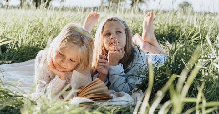 Hai cô bé đang nằm đọc sách trên cánh đồng hoa cỏ, dưới ánh nắng ban mai tuyệt đẹp.