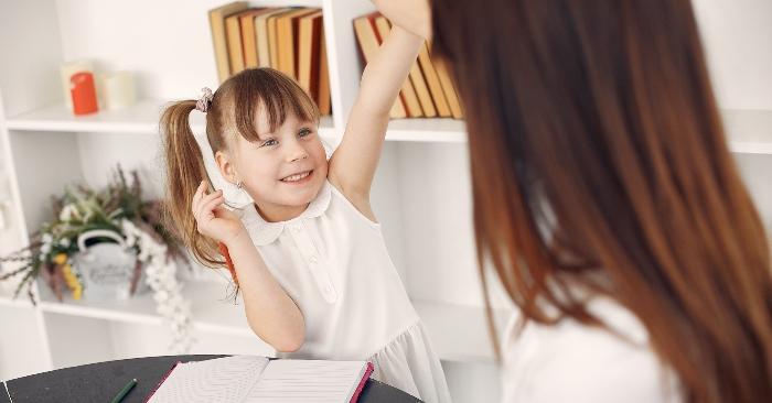 Bé  gái vui mừng khi được mẹ khen ngợi khi làm bài đúng.
