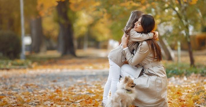 Trong công viên, người  mẹ đang ôm      cô con gái bé nhỏ trong vòng tay yêu thương.