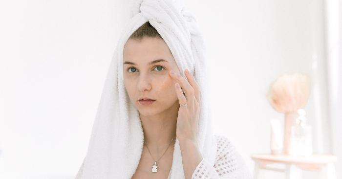 Người phụ nữ đang chăm sóc làn da mặt của mình với các sản phẩm chuyên dụng. Đặc biệt là vùng quanh mắt.