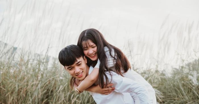 Người vợ cười hạnh phúc ôm choàng người chồng yêu thương.