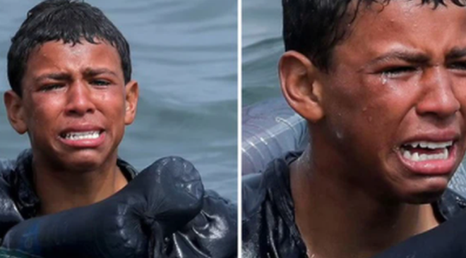 cậu bé di cư bật khóc giữa biển nước mênh mông