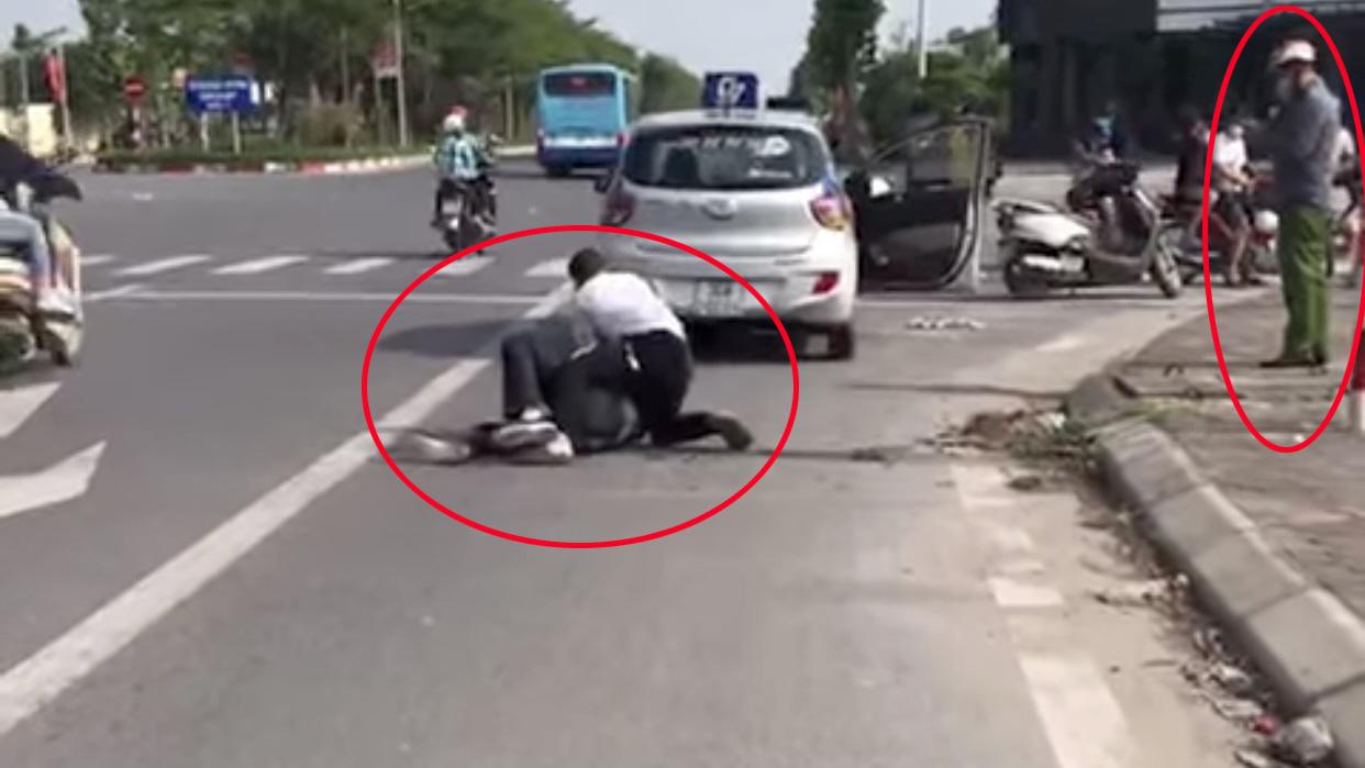 Đại úy Nguyễn Văn Lâm đứng bấm điện thoại trong khi tài xế taxi vật lộn với tên cướp