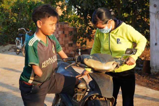 Cậu bé khuyết tay chân được mẹ chở đi đá bóng