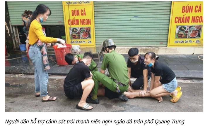 Người dân giúp công an khống chế thanh niên nghi ngáo đá (ảnh chụp màn hình báo Giao Thông).