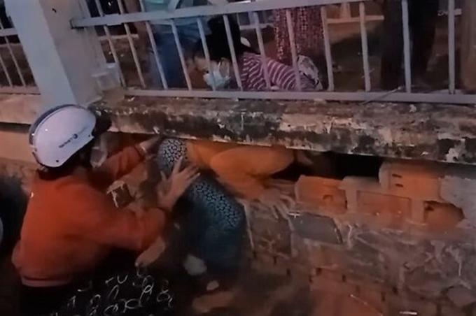 Các phụ nữ đang chui lỗ tường rào trốn ra bệnh viện, đêm 1/7 (ảnh: Cắt từ video người dân cung cấp)