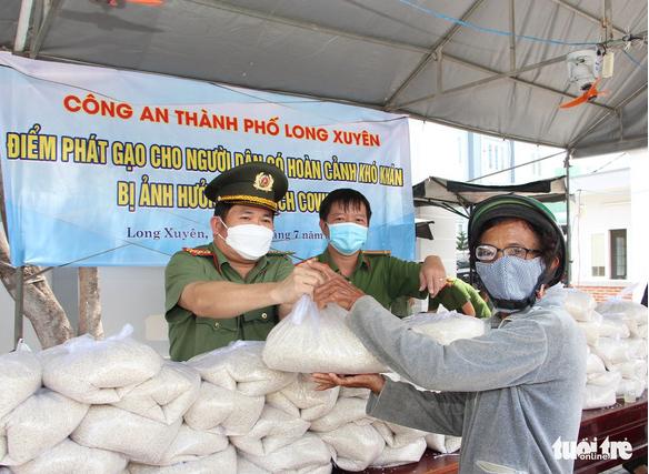 Giám đốc Công an tỉnh Đinh Văn Nơi trao tặng gạo cho người dân nghèo.