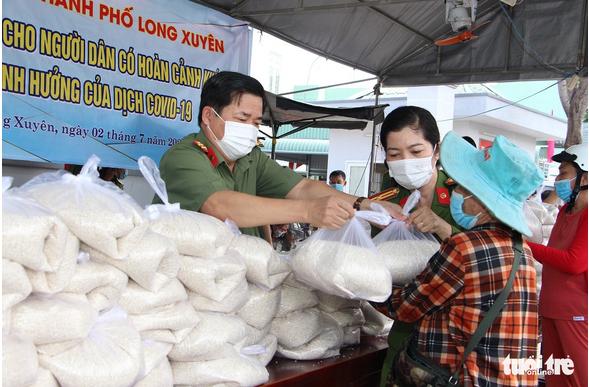 Lãnh đạo Công an TP Long Xuyên trao tặng gạo cho người dân gặp khó khăn.